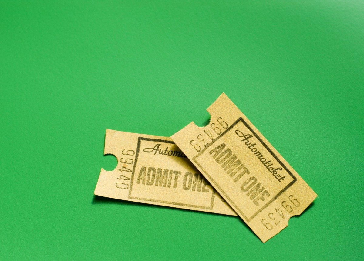 Two generic admission tickets or coupons for an event or entertainment on a green background with copyspace